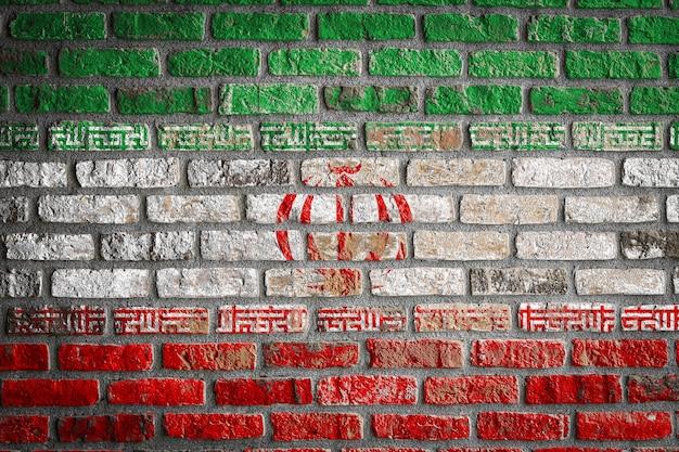Drapeau national de l'iran sur un vieux mur de briques