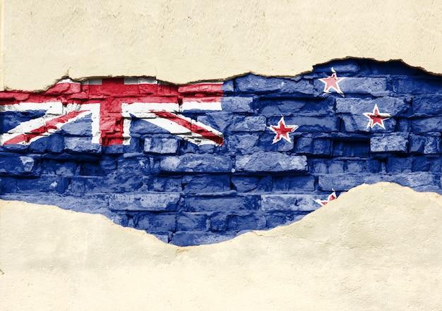 Drapeau national de la nouvelle-zélande sur un fond de brique. mur de briques avec plâtre partiellement détruit, arrière-plan ou texture.
