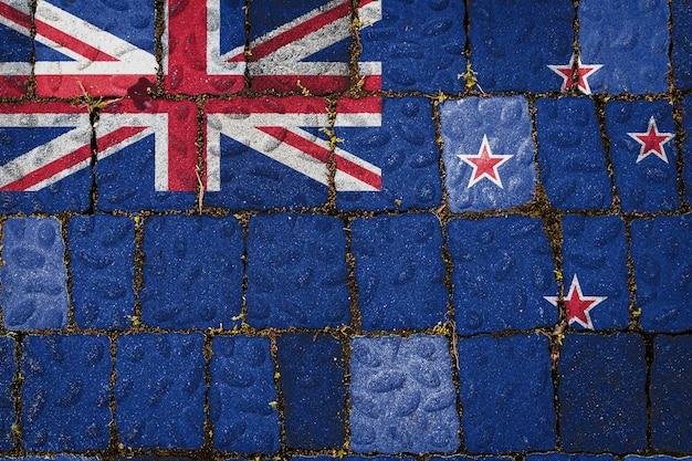 Drapeau national de la nouvelle-zélande sur fond de mur de pierre. bannière de drapeau sur fond de texture de pierre.