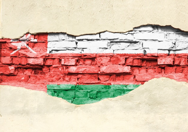 Drapeau national d'oman sur un fond de briques. mur de briques avec plâtre, arrière-plan ou texture partiellement détruit.