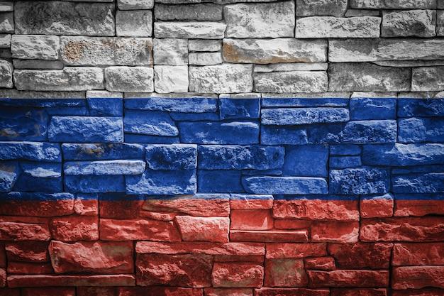 Drapeau national de la russie sur fond de mur de pierre. bannière de drapeau sur fond de texture de pierre