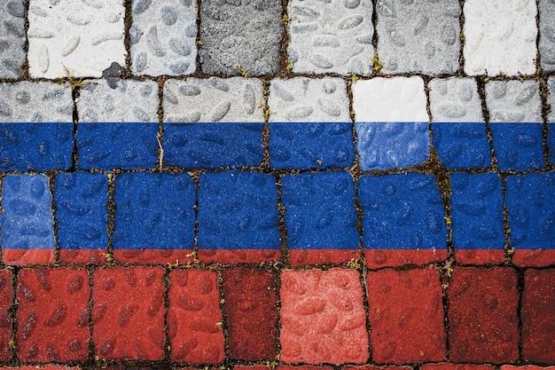 Drapeau national de la russie sur fond de mur de pierre. bannière de drapeau sur fond de texture de pierre.