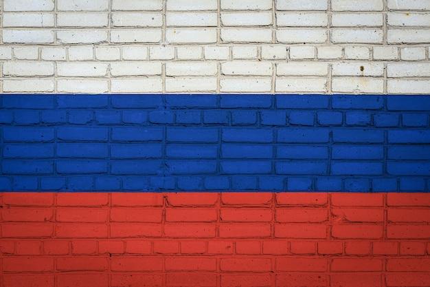 Drapeau national de la russie représentant en couleurs de peinture sur un vieux mur de briques. drapeau sur fond de mur de brique.