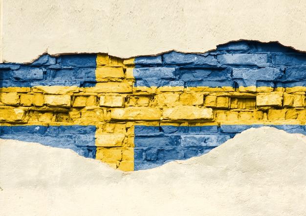 Drapeau national de la suède sur un fond de brique. mur de briques avec plâtre partiellement détruit, arrière-plan ou texture.