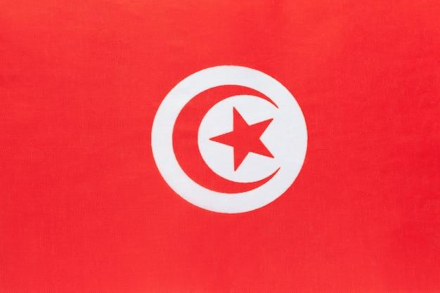 Drapeau national de la tunisie en tissu avec emblème. symbole du pays africain du monde international.