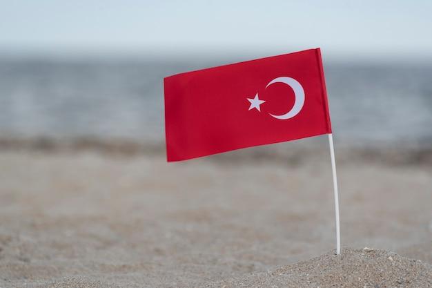 Drapeau national de la turquie sur le sable de la mer