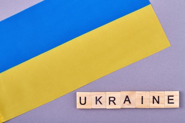 Drapeau national de l'ukraine. couleurs bleues et jaunes sur la bannière. blocs de lettres en bois isolés sur fond violet.