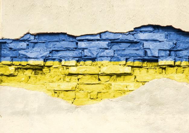 Drapeau national de l'ukraine sur un fond de brique. mur de briques avec plâtre partiellement détruit, arrière-plan ou texture.