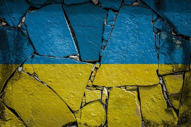 Drapeau national de l'ukraine représentant en couleurs de peinture sur un vieux mur de pierre. bannière de drapeau sur fond de mur cassé.