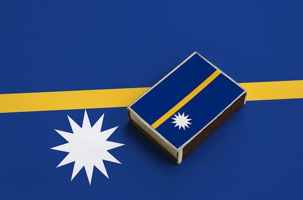 Le drapeau de nauru est représenté sur une boîte d'allumettes qui repose sur un grand drapeau