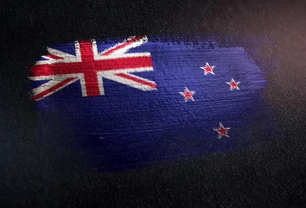 Drapeau néo-zélandais fait de peinture brosse métallique sur mur sombre grunge