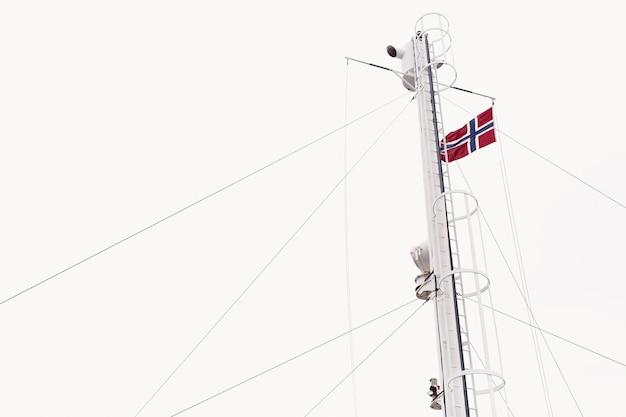 Drapeau de la norvège sur le vent sous le ciel blanc