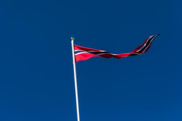 Drapeau norvégien contre le ciel bleu, drapeau de la norvège