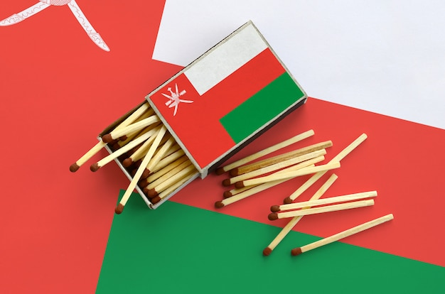Le drapeau d'oman est affiché sur une boîte d'allumettes ouverte, à partir de laquelle plusieurs allumettes tombent et repose sur un grand drapeau.