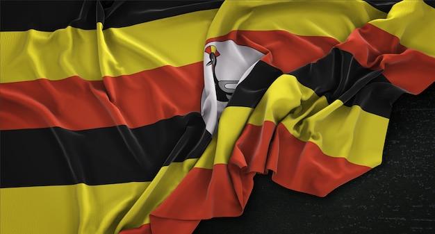 Drapeau de l'ouganda enroulé sur fond sombre 3d render