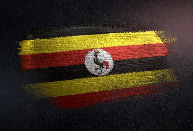 Drapeau de l'ouganda fait de peinture brosse métallique sur mur sombre grunge