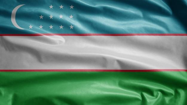 Drapeau de l'ouzbékistan dans le vent. modèle ouzbek soufflant, soie douce et lisse. fond d'enseigne de texture de tissu de tissu.