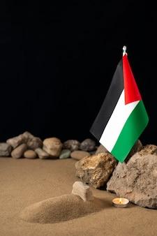 Drapeau palestinien avec des pierres sur une surface sombre
