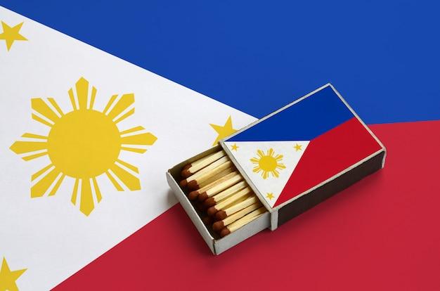 Le drapeau des philippines est affiché dans une boîte d'allumettes ouverte, qui est remplie d'allumettes et repose sur un grand drapeau
