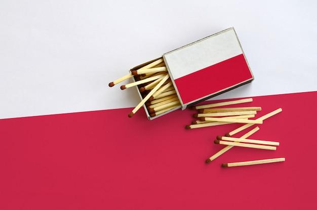 Le drapeau de la pologne est montré sur une boîte d'allumettes ouverte, à partir de laquelle plusieurs matches tombent et repose sur un grand drapeau