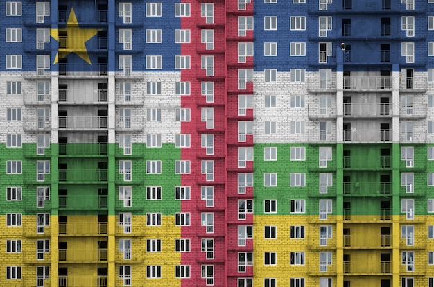 Drapeau de la république centrafricaine représenté en couleurs de peinture sur un immeuble résidentiel à plusieurs étages en construction.