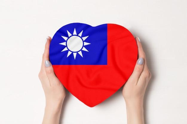 Drapeau de la république de chine sur une boîte en forme de coeur dans une main féminine