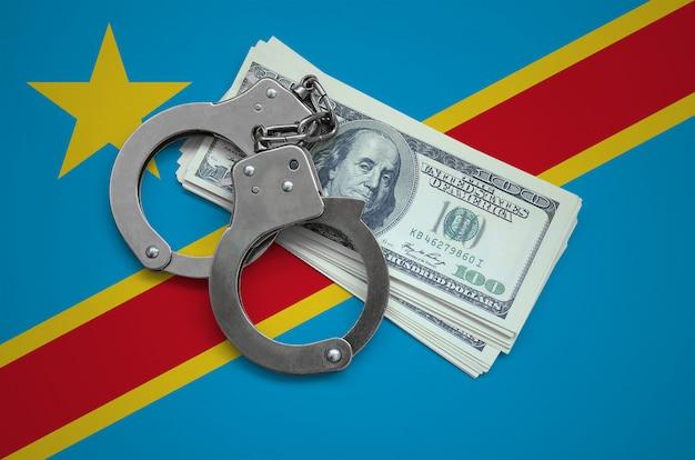 Drapeau de la république démocratique du congo avec des menottes et un paquet de dollars. la corruption monétaire dans le pays. crimes financiers