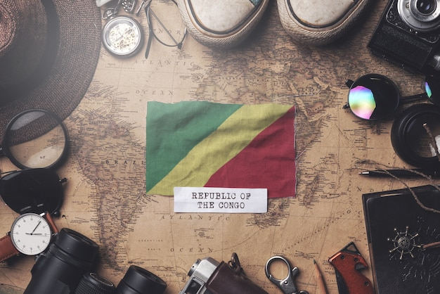 Drapeau de la république du congo entre les accessoires du voyageur sur l'ancienne carte vintage. tir aérien