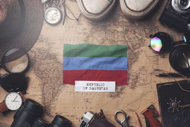 Drapeau de la république du daghestan entre les accessoires du voyageur sur l'ancienne carte vintage. tir aérien