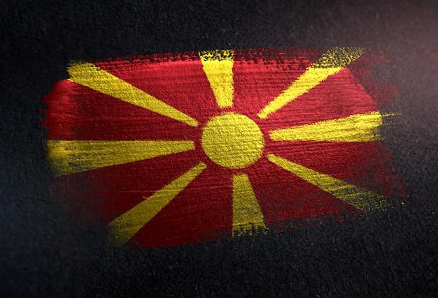 Drapeau de la république de macédoine fait de peinture brosse métallique sur mur sombre grunge