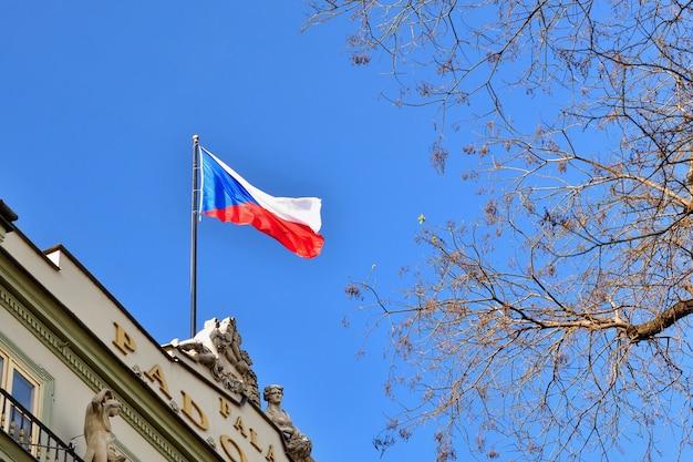 Le drapeau de la république tchèque sur un bâtiment avec le ciel bleu et le soleil en arrière-plan.