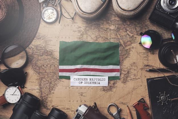 Drapeau de la république tchétchène d'ichkeria entre les accessoires du voyageur sur l'ancienne carte vintage. tir aérien