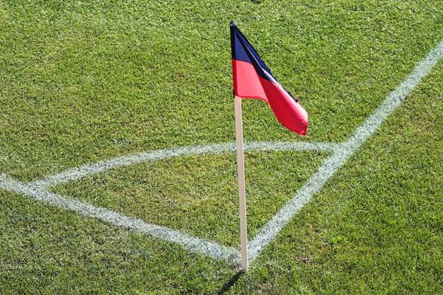 Un drapeau rouge et bleu à un coin du stade de football et le coin d'un terrain de football