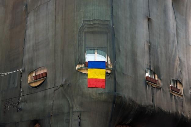 Drapeau roumain dans la fenêtre. couper dans le filet pour la vue de la fenêtre.