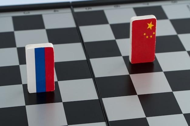 Drapeau de symboles de la russie et de la chine sur l'échiquier. le concept de jeu politique.