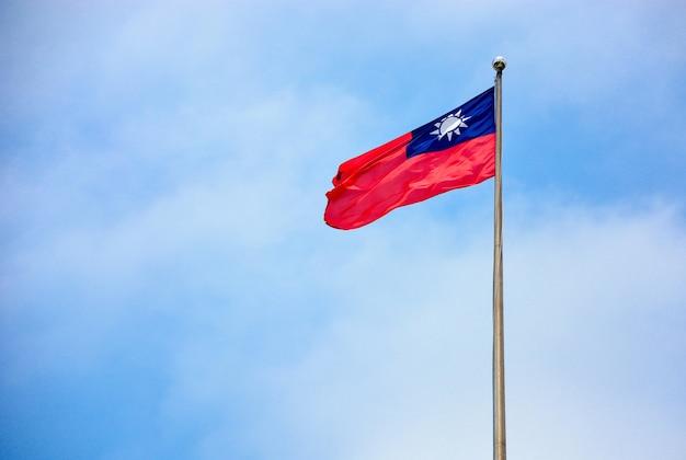Drapeau taiwan (république de chine) dans le vent sur le mât avec fond de ciel et nuages bleu