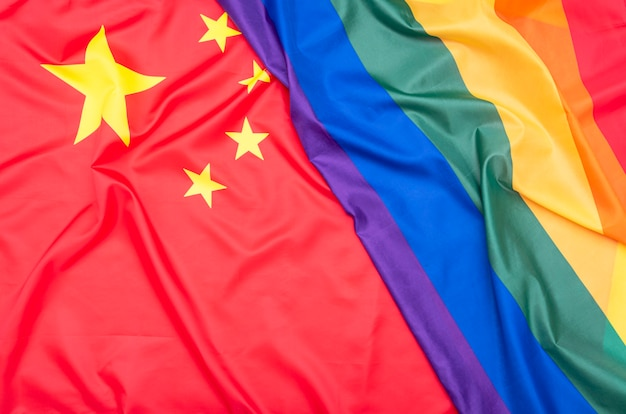 Drapeau en tissu naturel de la chine et drapeau arc-en-ciel lgbt comme texture ou arrière-plan, photo conceptuelle sur les droits de l'homme
