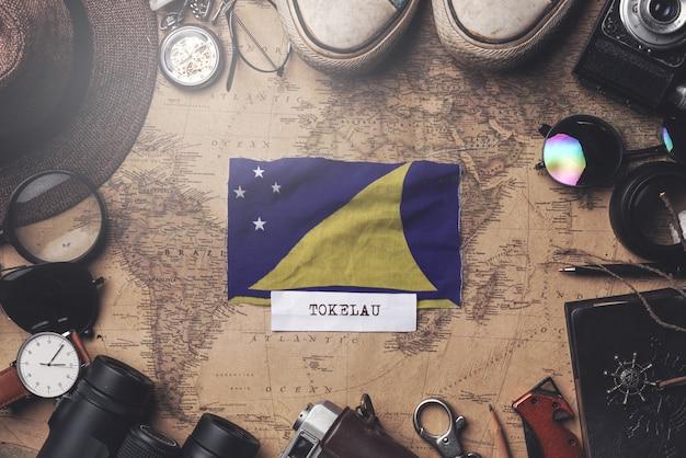 Drapeau des tokélaou entre les accessoires du voyageur sur l'ancienne carte vintage. tir aérien