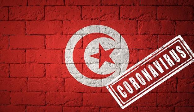 Drapeau de la tunisie aux proportions originales. estampillé du coronavirus. texture de mur de briques. notion de virus corona. au bord d'une pandémie covid-19 ou 2019-ncov.