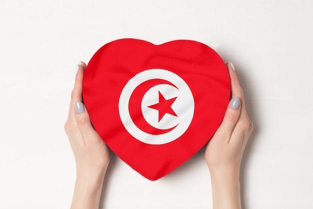Drapeau de la tunisie sur une boîte en forme de coeur dans une main féminine