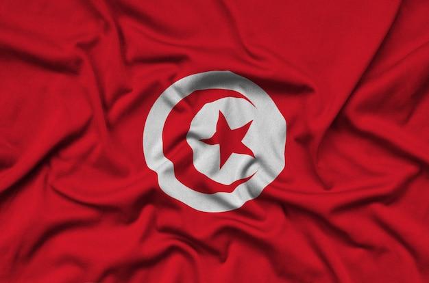 Le drapeau de la tunisie est représenté sur un tissu de sport avec de nombreux plis.