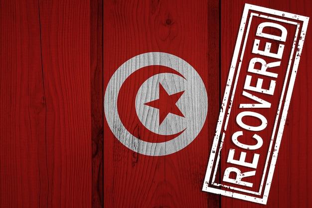 Drapeau de la tunisie qui a survécu ou récupéré des infections de l'épidémie de virus corona ou de coronavirus. drapeau grunge avec timbre récupéré