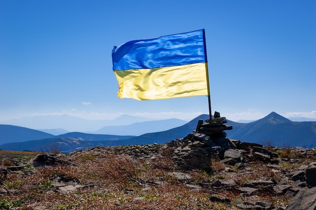 Drapeau de l'ukraine au sommet d'une montagne dans les carpates. tourisme en ukraine
