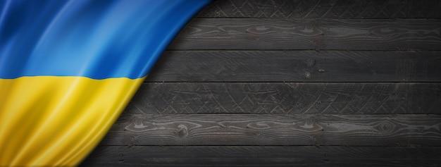Drapeau de l'ukraine sur le mur en bois noir. panoramique.