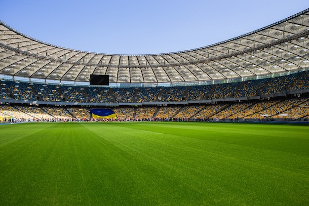 Drapeau ukrainien et foule de personnes sur le stade olympique de football avec des bancs jaunes et bleus