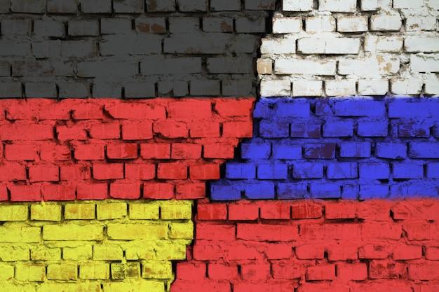 Drapeaux de l'allemagne et de la russie sur le mur de briques avec une grande fissure au milieu. symbole de problèmes entre pays