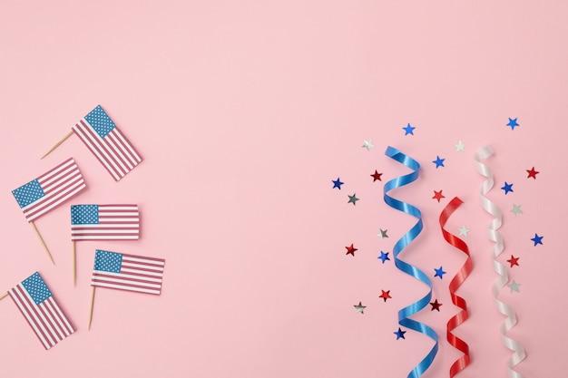 Drapeaux américains, rubans bouclés et étoiles sur surface rose