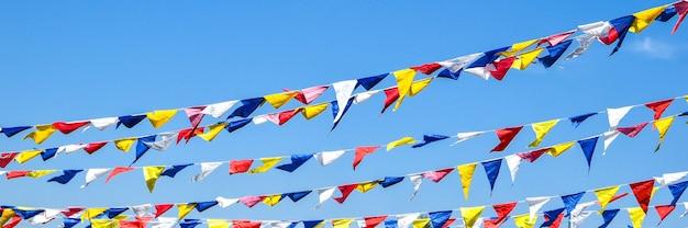 Drapeaux arc-en-ciel de fête multicolores sur ciel bleu pour la célébration.
