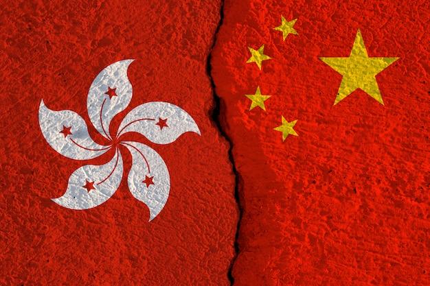 Les drapeaux de la chine et de hong kong impriment un écran sur un mur fissuré.
