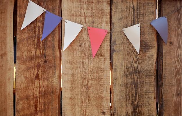 Drapeaux colorés de fête sur le fond grunge en bois.